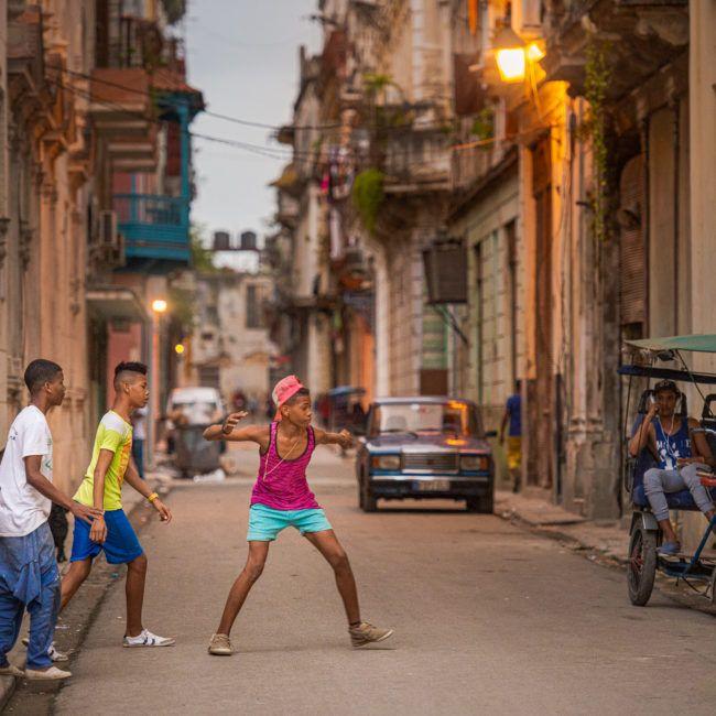 Des jeunes jouent au ballon dans la rue