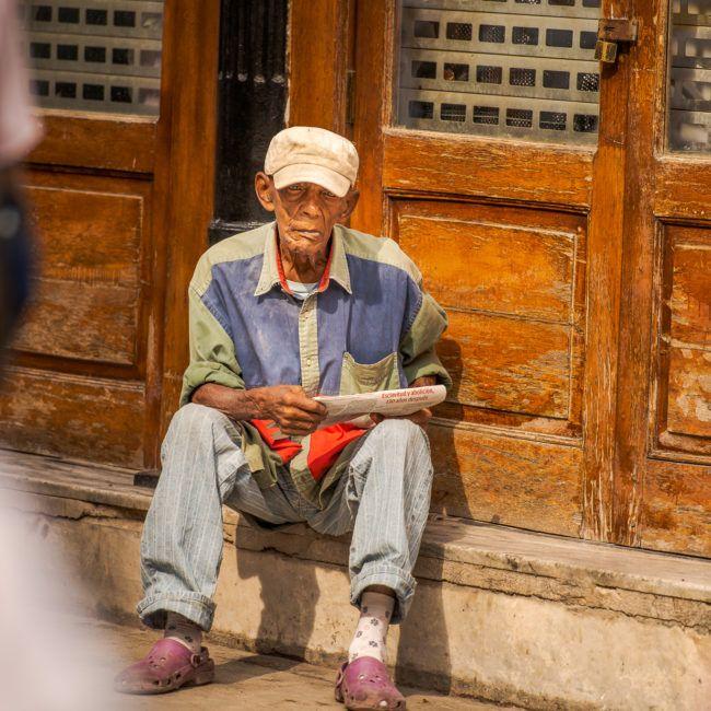 Un homme lit le journal dans la rue
